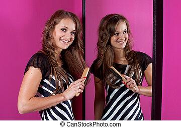 Young woman correcting hairs at mirror