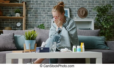Young woman coughing in paper tissue wiping nose feeling sick at home
