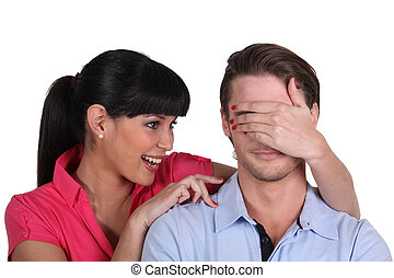Young woman covering a man's eyes