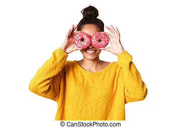 Young woman covering her eyes with donut