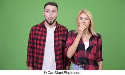 Young woman covering mouth while looking guilty with young...