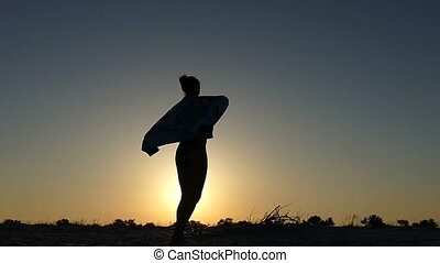 Young woman covers her body with a towel at sunset in slo-mo