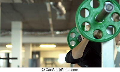 young woman crouching with a barbell in the gym