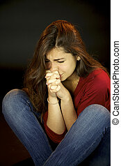 Young woman crying in the dark