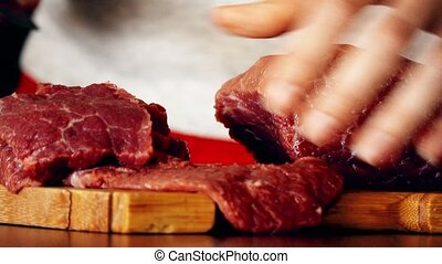 Young woman cuts raw red meat on the wooden cutting board. 4K close-up shot