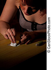 Young woman cutting heroin or cocaine lines