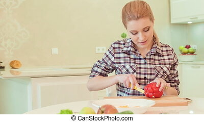 Young woman cutting paprika - that will be delicious salad....