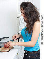 Young woman cutting tomatoe