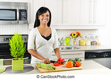 Young woman cutting vegetables in kitchen - Smiling black ...