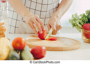 Young woman cutting vegetables in kitchen