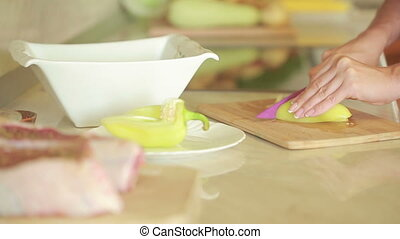 Young woman cutting vegetables in the kitchen for fresh salad. pepper