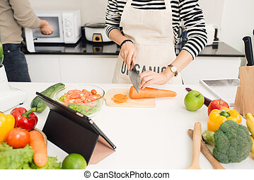 Young woman cutting vegetables in the kitchen.