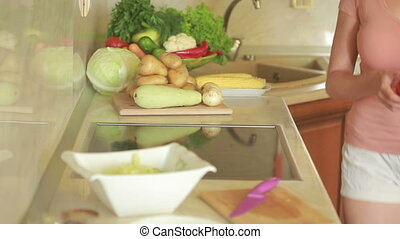 Young woman cutting vegetables in the kitchen for fresh salad. tomato