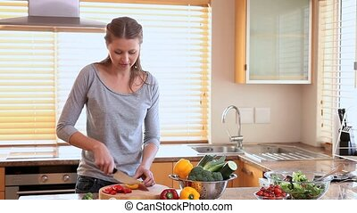 Young woman cutting vegetables