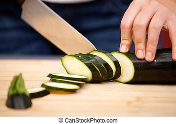 Young woman cutting zucchini