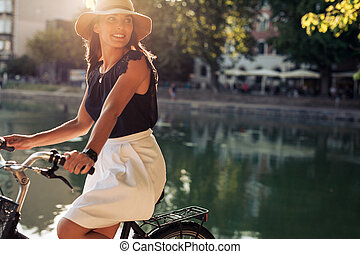 Young woman cycling by a pond