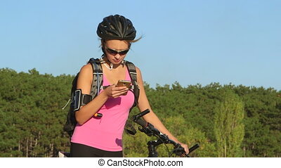 Young woman cyclist on her mountain bike using smart phone outdoors