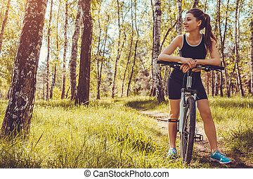 Young woman cyclist riding a mountain bicycle in spring forest. Girl having rest