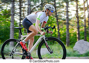 Young Woman Cyclist Riding Road Bicycle on the Free Road in the Forest at Hot Summer Day. Healthy Lifestyle Concept.