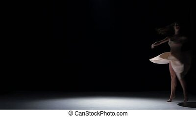 Young woman dancer dancing contemporary dance moves, on black, shadow