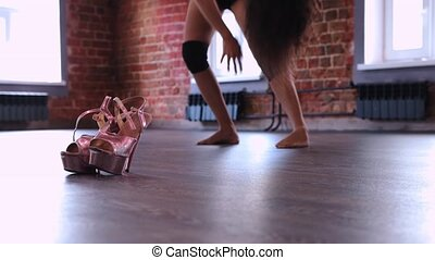 Young woman dancer warming up her body before dancing - high heels near her. Mid shot