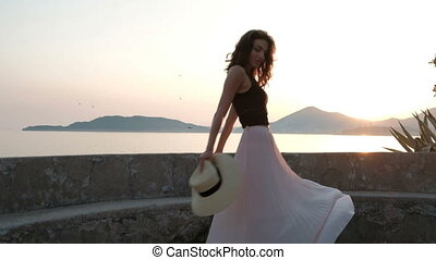 Young woman dances a view to the sea on summer evening outdoor Spectacular brunette with wavy hair