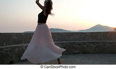 Young woman dances by fence near sea shore in evening.