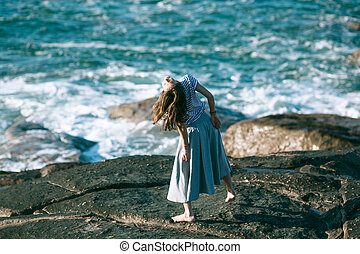 Young woman dances freely on the Atlantic ocean coast.