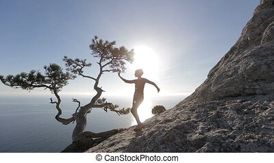 Young woman dancing and running on a mountain. Lady on the summit in beautiful scenery above the sea.
