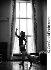 young woman dancing at home by the window
