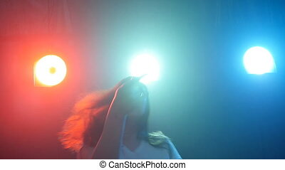 Young woman dancing in a disco color light