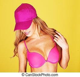 Young woman dancing in a pink bikini