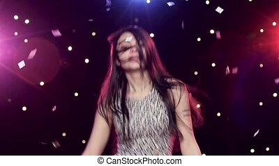 Young woman dancing in front disco style lights glitter confetti