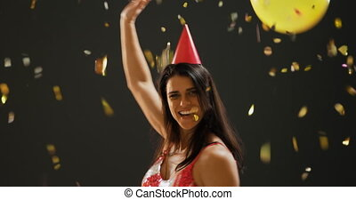 Young woman dancing in party hat - Front view close up of a ...