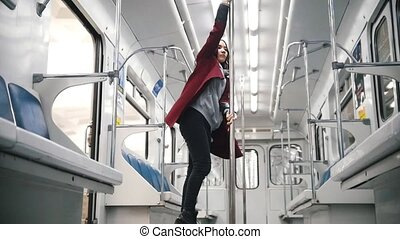 Young woman dancing in subway train - Young woman in red...