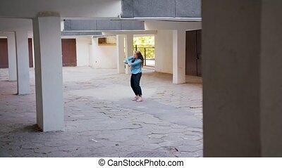 Young Woman Dancing in the Courtyard - A young woman dancing...