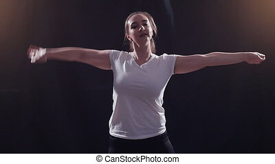 Young woman dancing on a black background