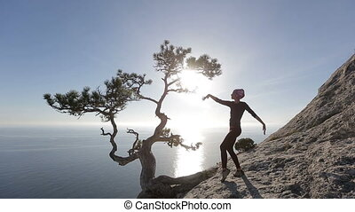 Young woman dancing on a mountain above the sea. Lady on the summit in beautiful scenery .