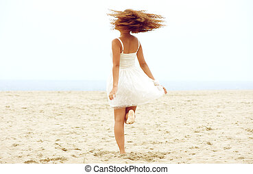 Young woman dancing on the sand at the beach