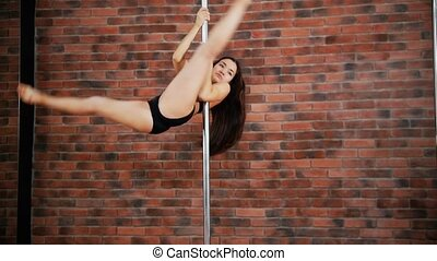 Young woman dancing pole dance in the studio
