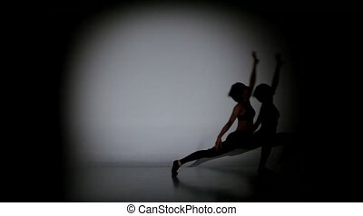 Young woman dancing sexy contemporary dance on black background, spot light