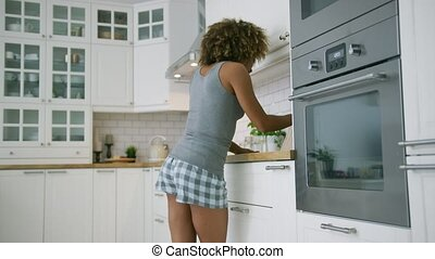 Young woman dancing while cooking