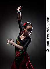 young woman dancing with castanets on black