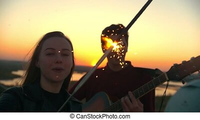 Young woman dancing with sparkler in front of boyfriend playing guitar outdoors at sunset