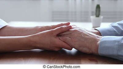Young woman daughter or doctor holding old man hands, closeup