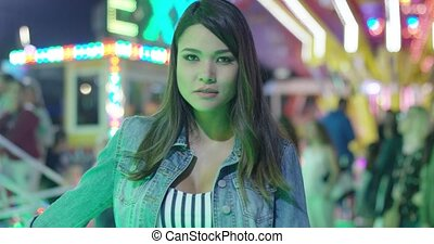 Young woman daydreaming at a funfair standing staring up off...