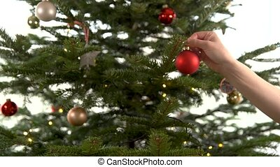 woman decorates a Christmas tree in the pre-Christmas period...