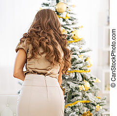 Young woman decorating christmas tree. rear view