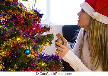decorating - young woman decorating christmas tree