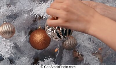 Young woman decorating Christmas tree. New year preparation, close up